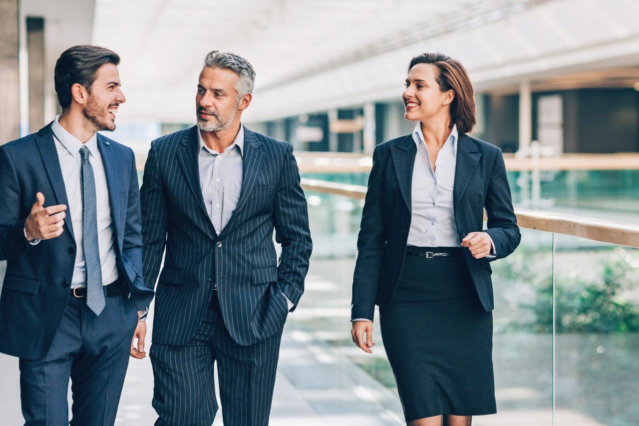 Mixed age group of business persons walking and talking